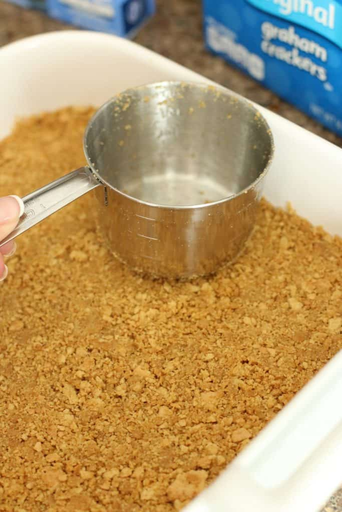 pressing graham cracker crumbs in cake pan with a measuring cup
