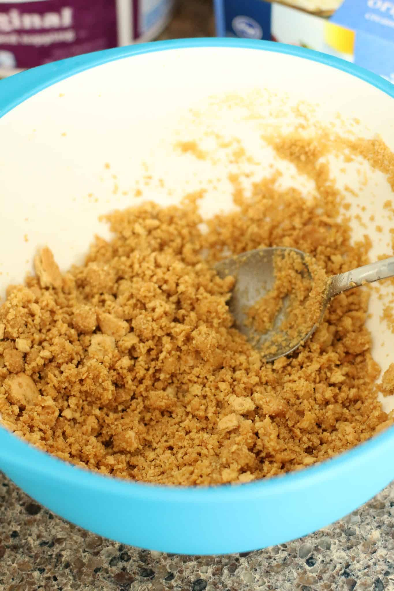 graham crackers, sugar, butter mixed together with a spoon in a bowl