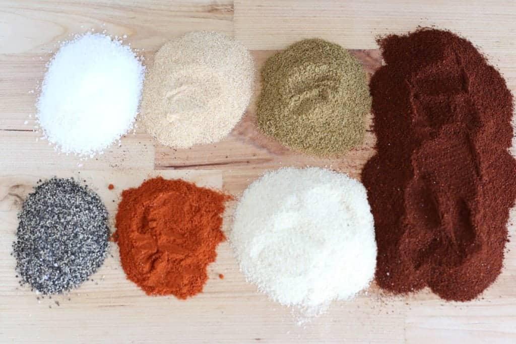 taco seasonings laid out on a wooden cutting board: chili powder, onion powder, ground cumin, garlic powder, smoked paprika, kosher (or sea) salt, black pepper
