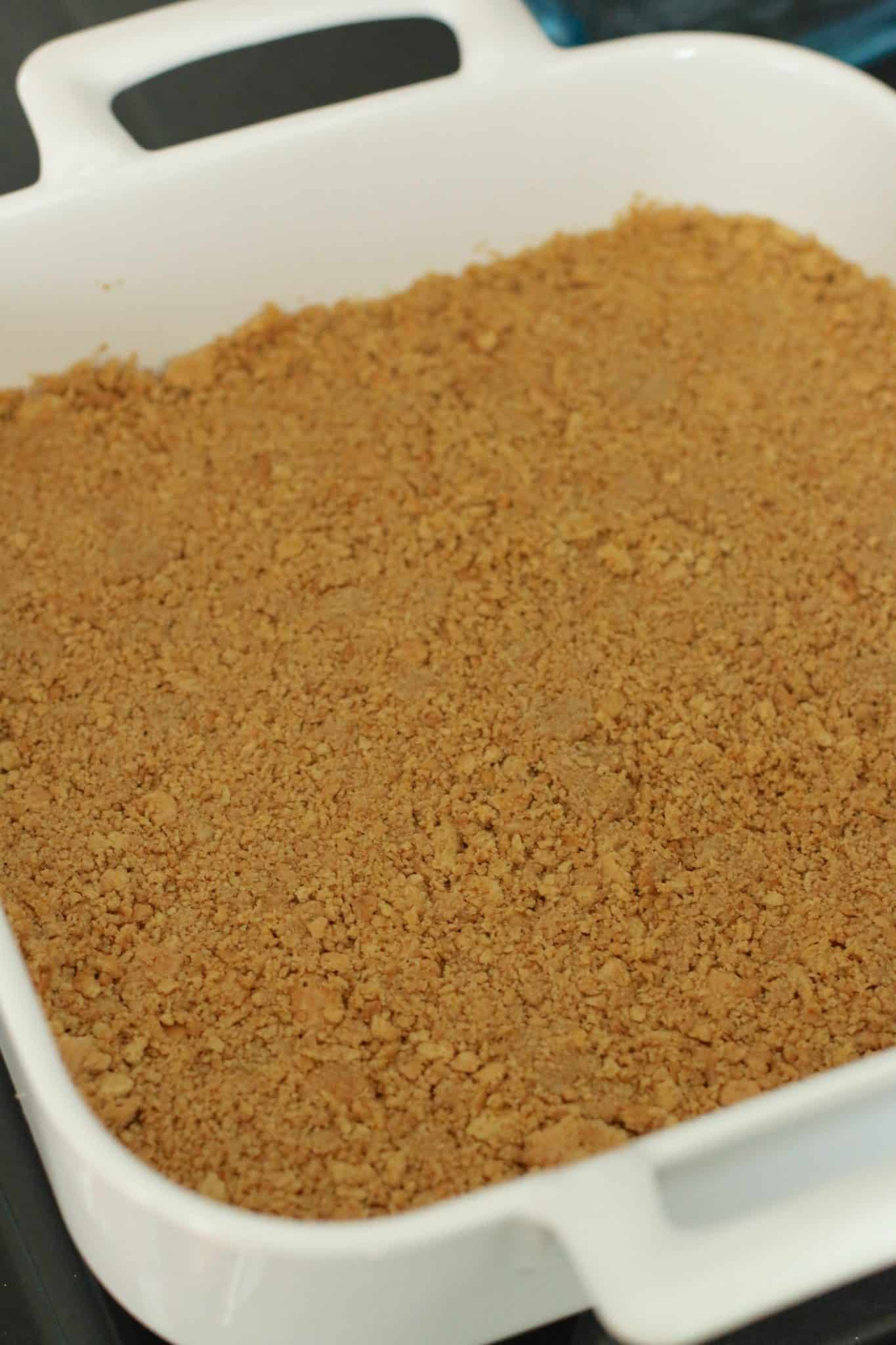 baked graham cracker crumb in the bottom of a square, white baking dish