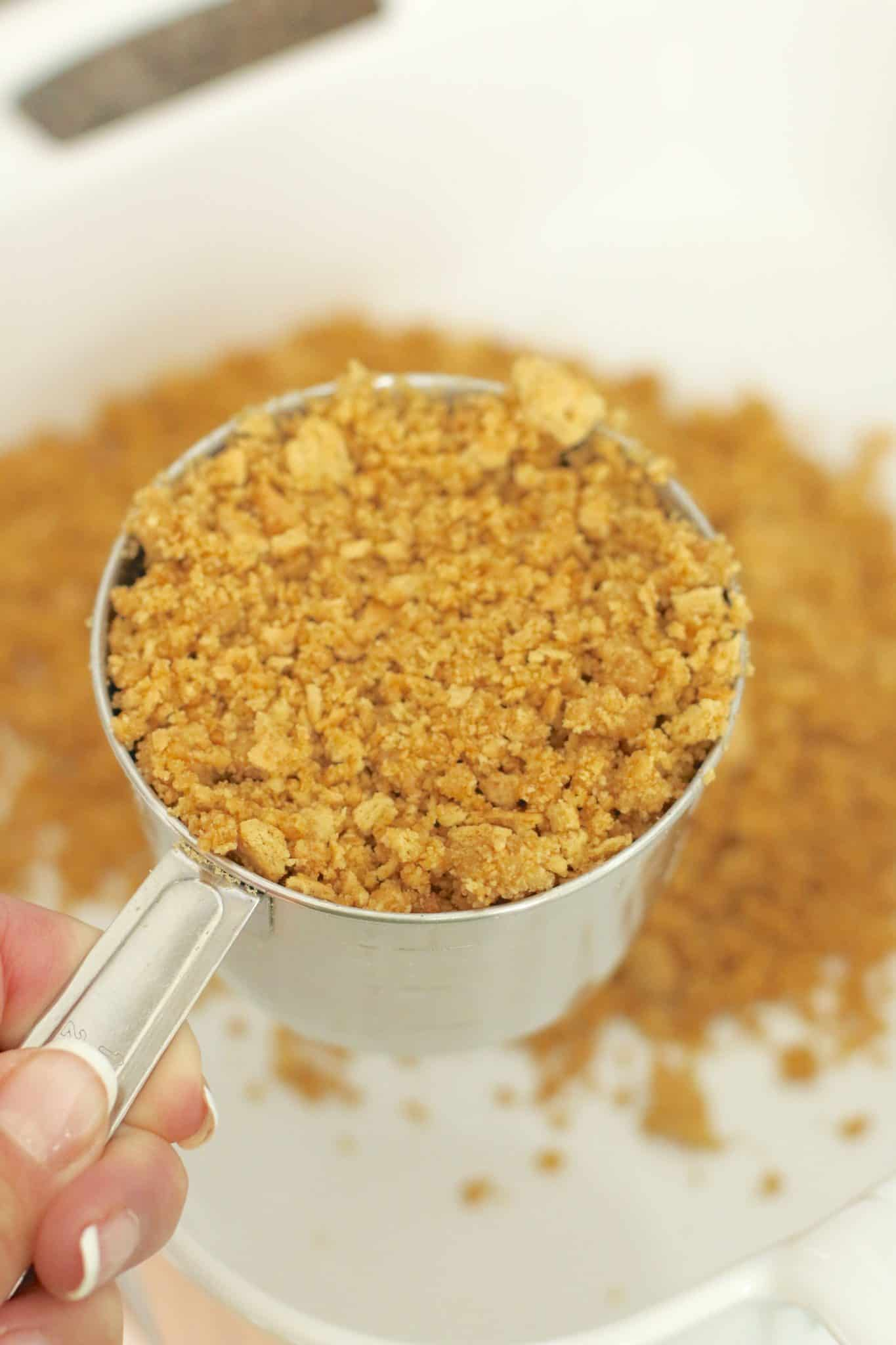 measuring graham cracker crust in a silver measuring cup