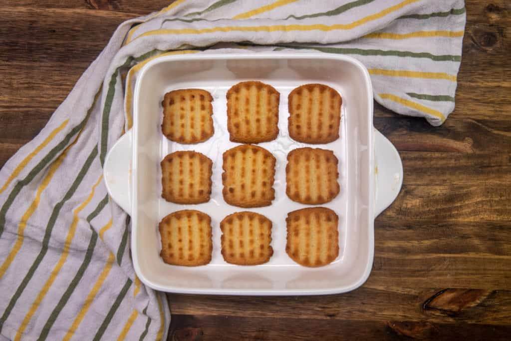 lemon-dipped shortbread cookies layered into the bottom of a white square baking dish