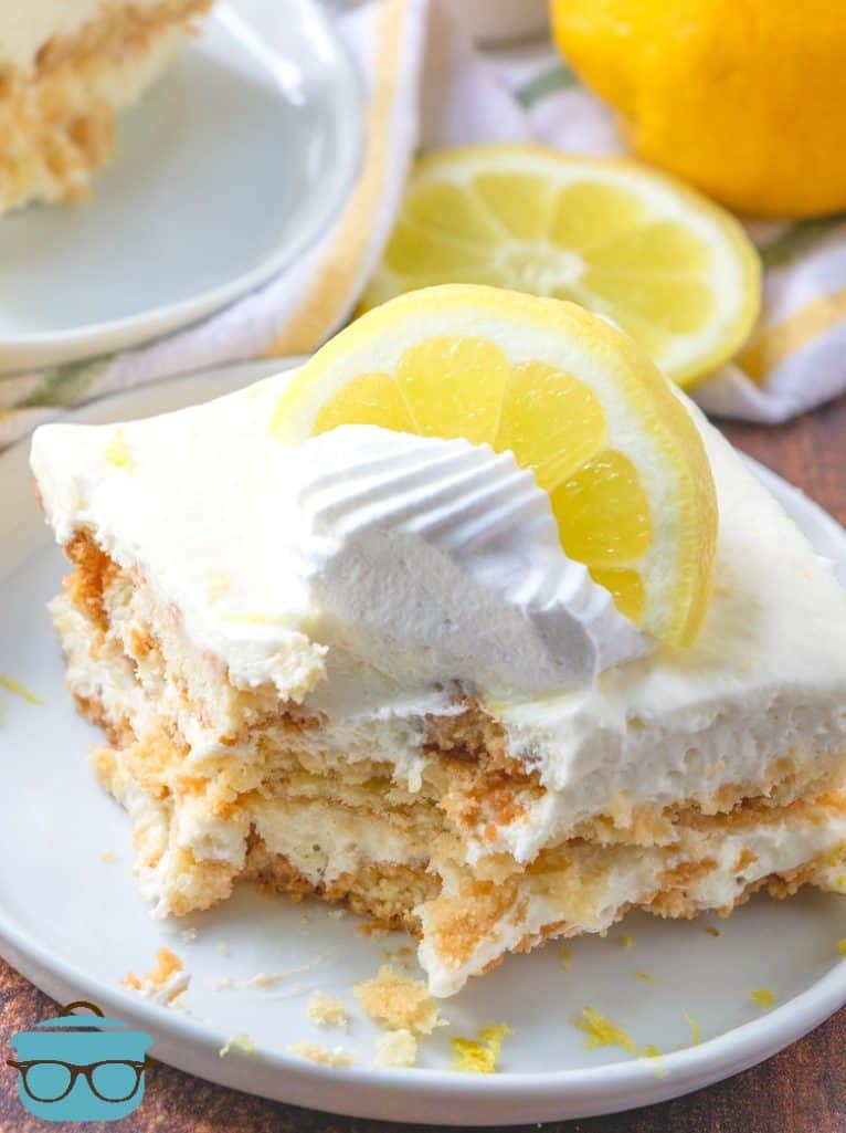 No-Bake Lemon Icebox Cake slice served on a white plate topped with a dollop of whipped cream and a lemon slice