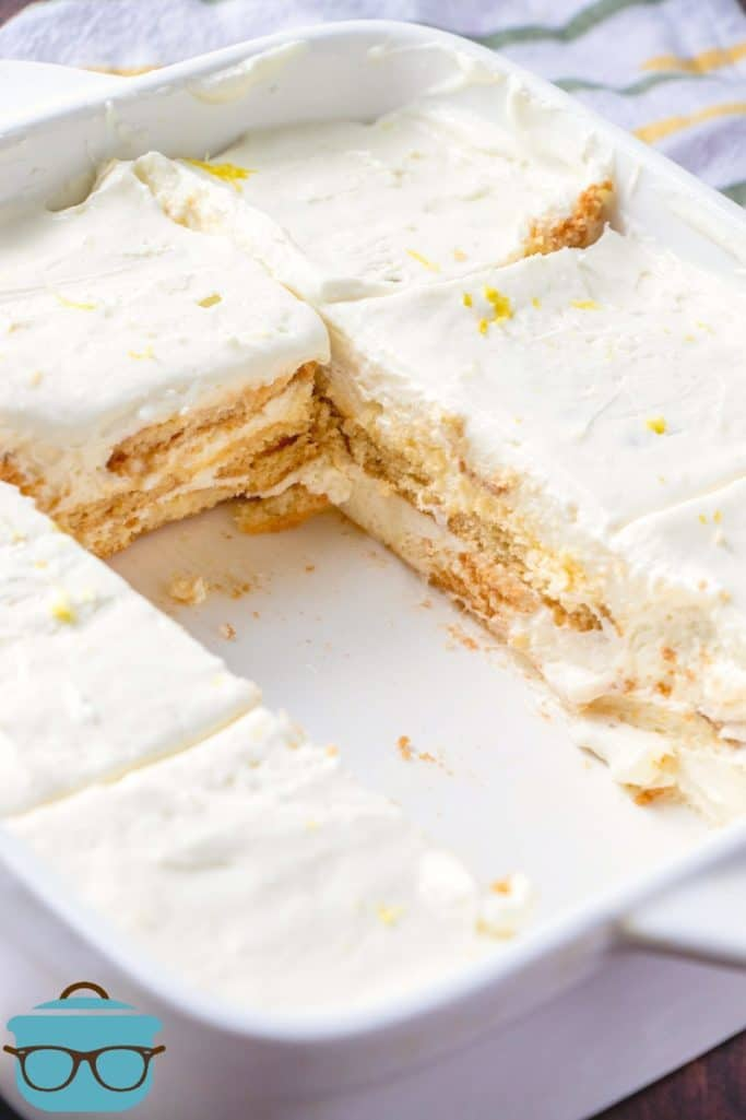 lemon icebox cake shown in a white serving dish, cut into slices with two slices missing