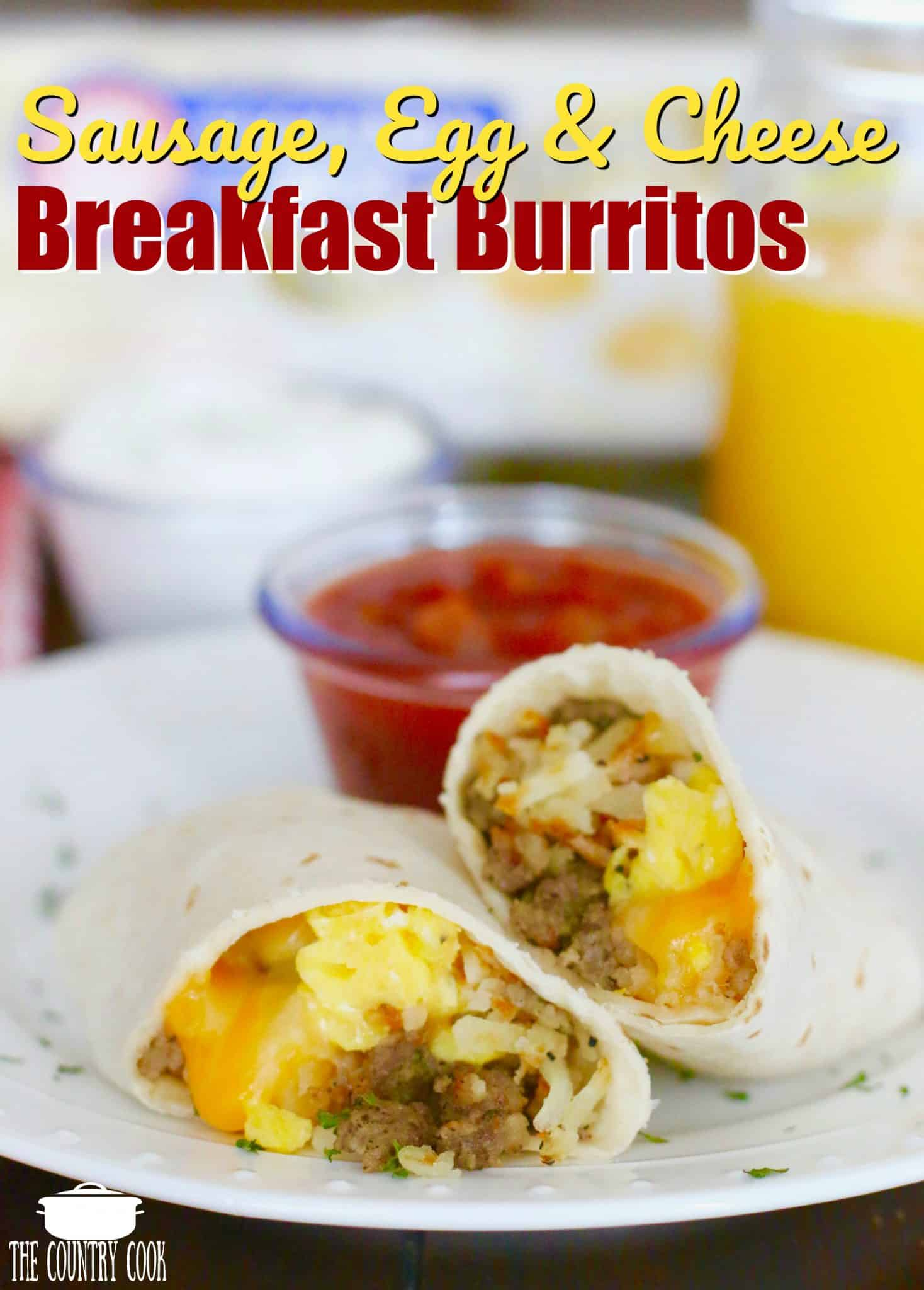 Sausage, Egg & Cheese Breakfast Burritos (freezer friendly) recipe from The Country Cook. Sliced burrito shown on a white plate with salsa and sour cream in the background.