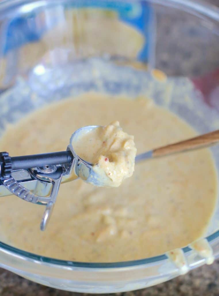using a spring loaded scooper to scoop up Mexican cornbread batter mix