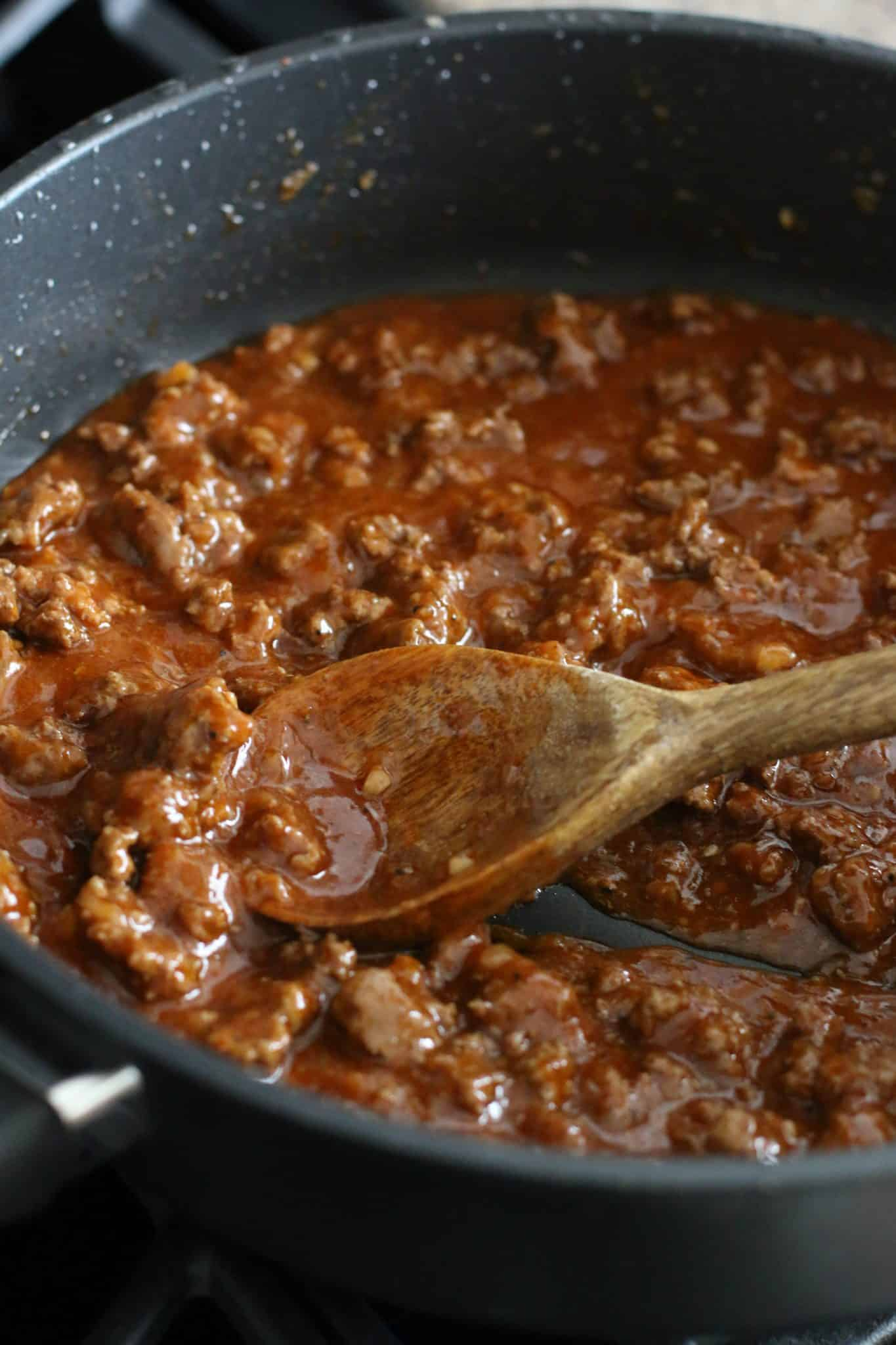 incorporating enchilada sauce into taco ground beef with a wooden spoon.