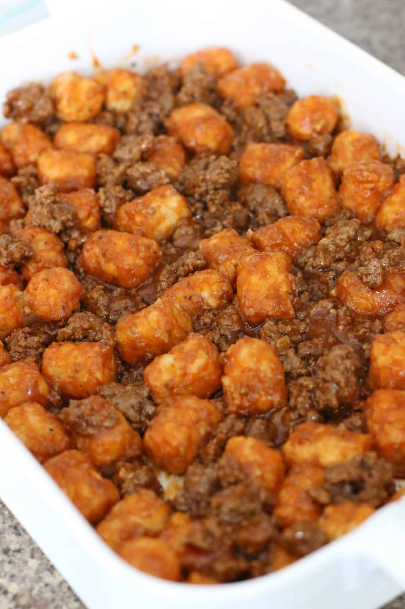 """spreading tater tot/ground beef mixture into a 9"""" by 13"""" baking dish."""