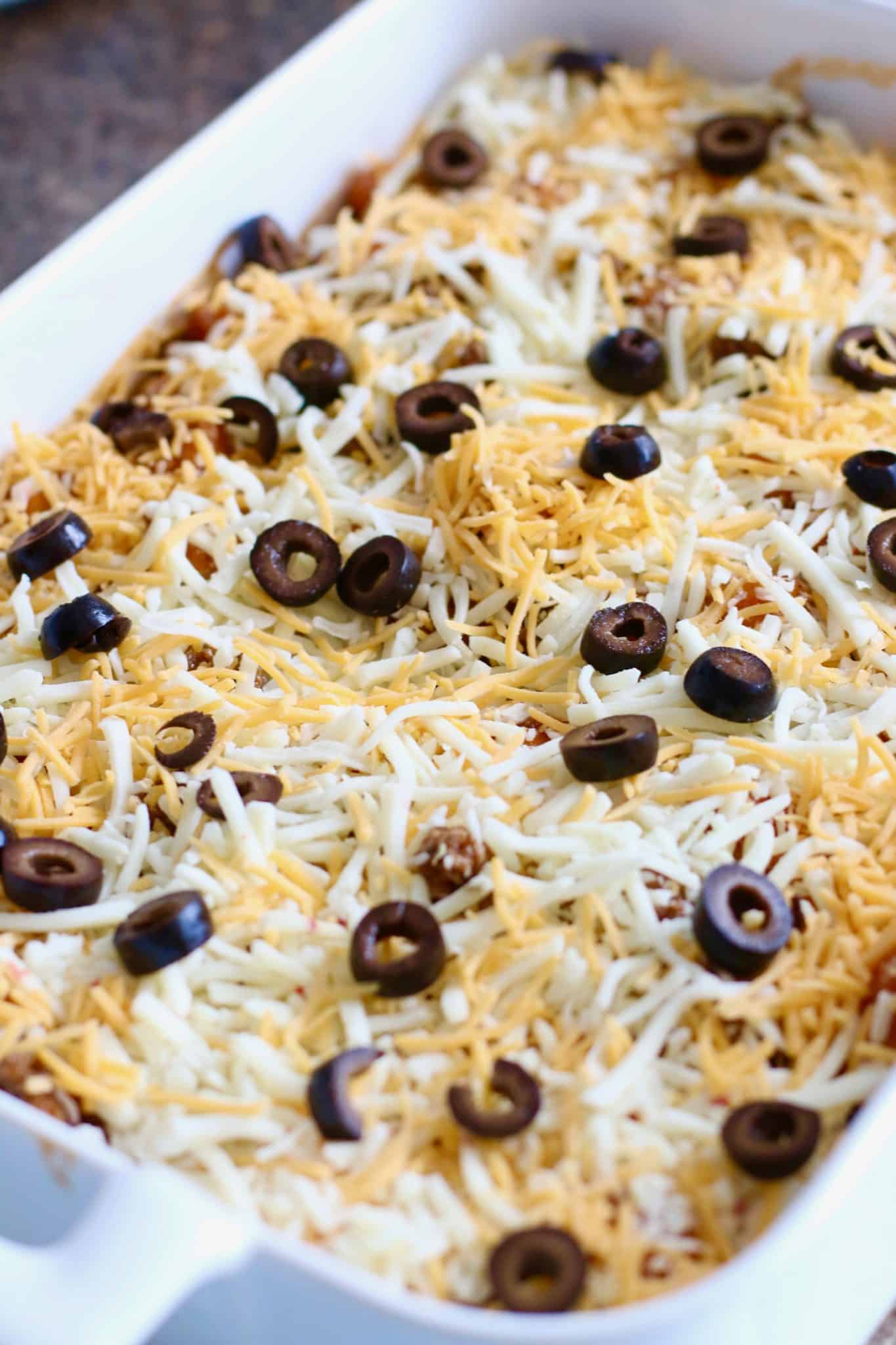shredded cheese and sliced olives topping enchilada casserole.