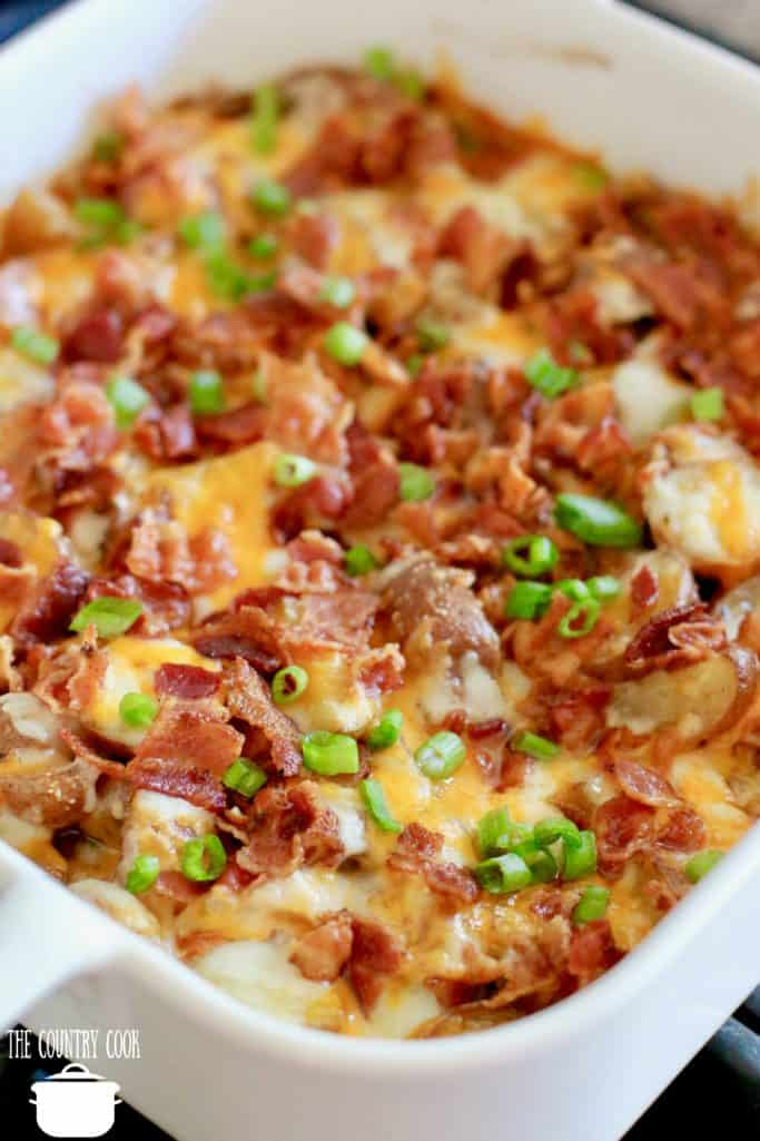 Bacon Cheese Little Potatoes in a square pan topped with bacon and sliced green onions