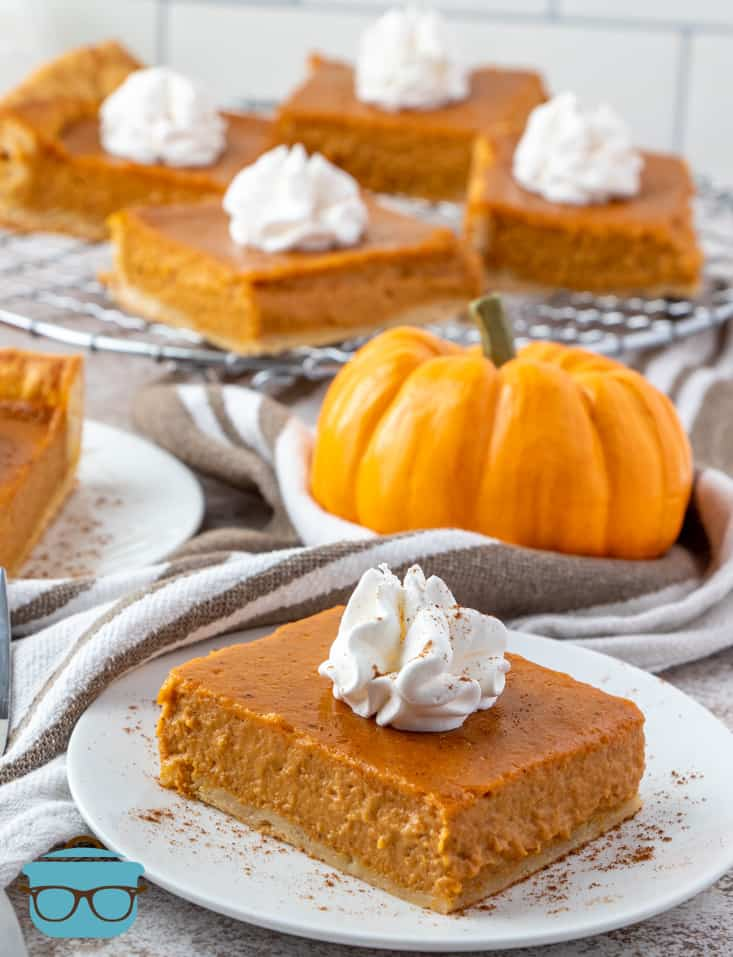 slices of Pumpkin Pie Bars on a plate and on a wire rack in the background