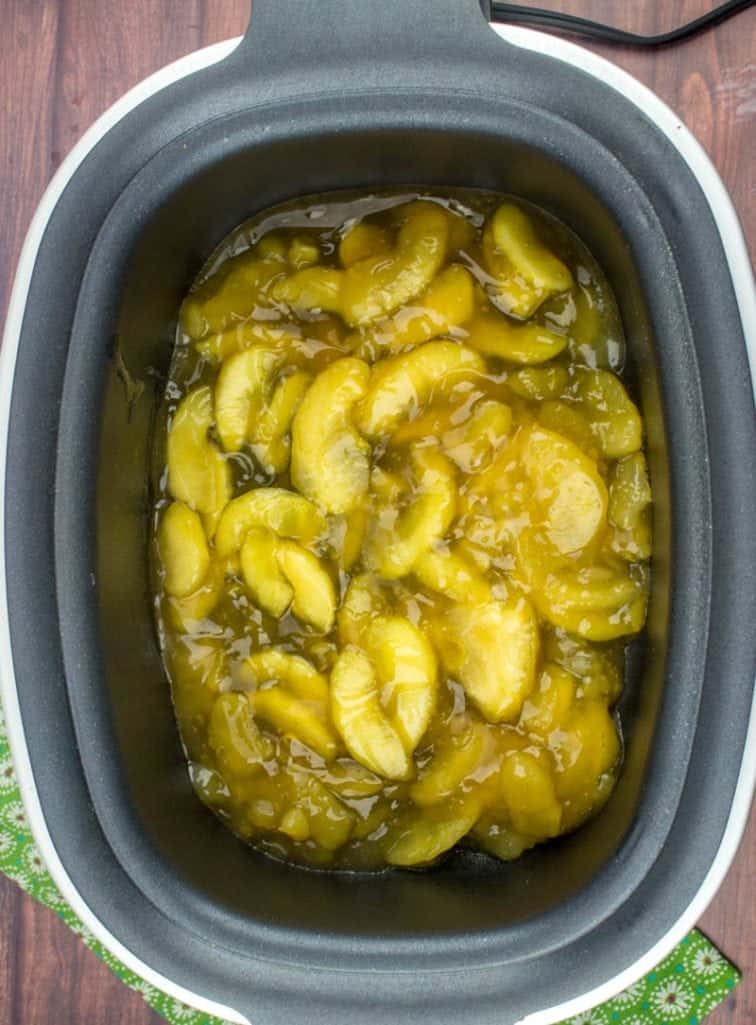 apple pie filling in the bottom of a slow cooker