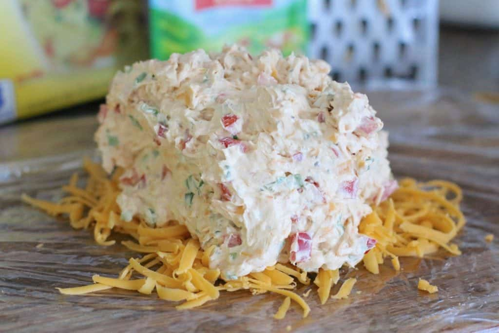 vegetable cheeseball mixture spread on top of cheese and plastic wrap