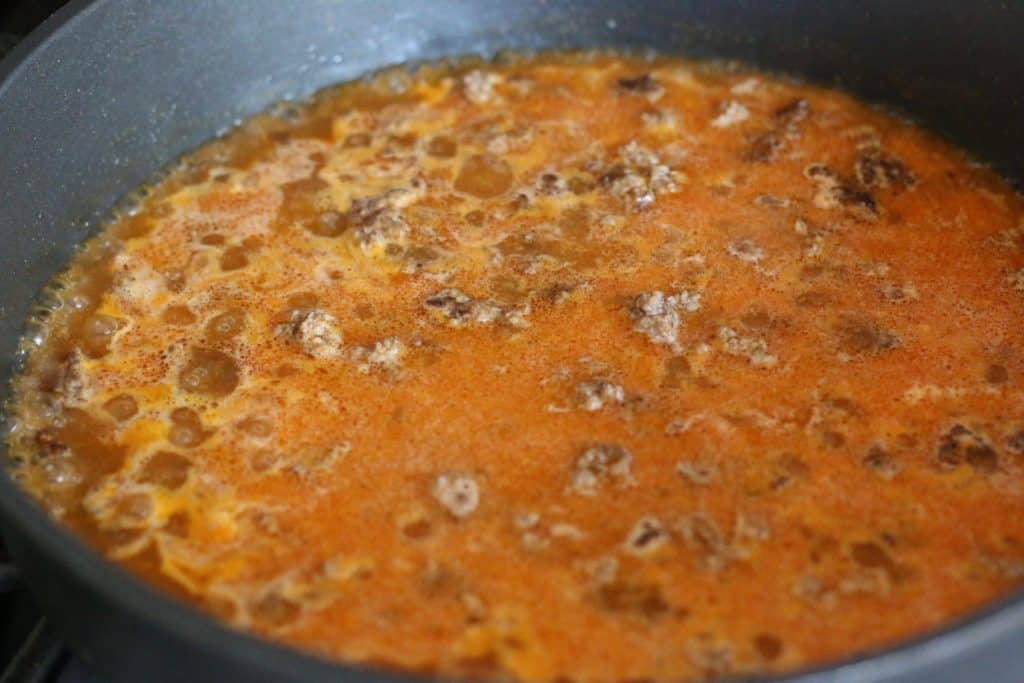 cooked ground beef, water and taco seasoning in a large skillet coming to a rolling boil