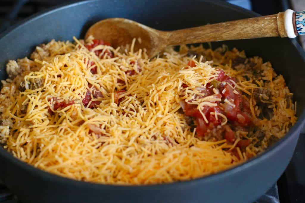 shredded cheese and salas added to taco rice mixture in large skillet
