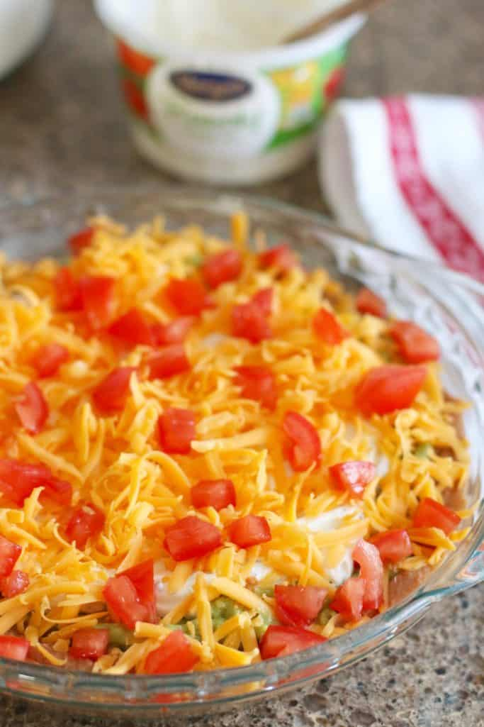 mexican layer dip topped with shredded cheese and diced tomatoes