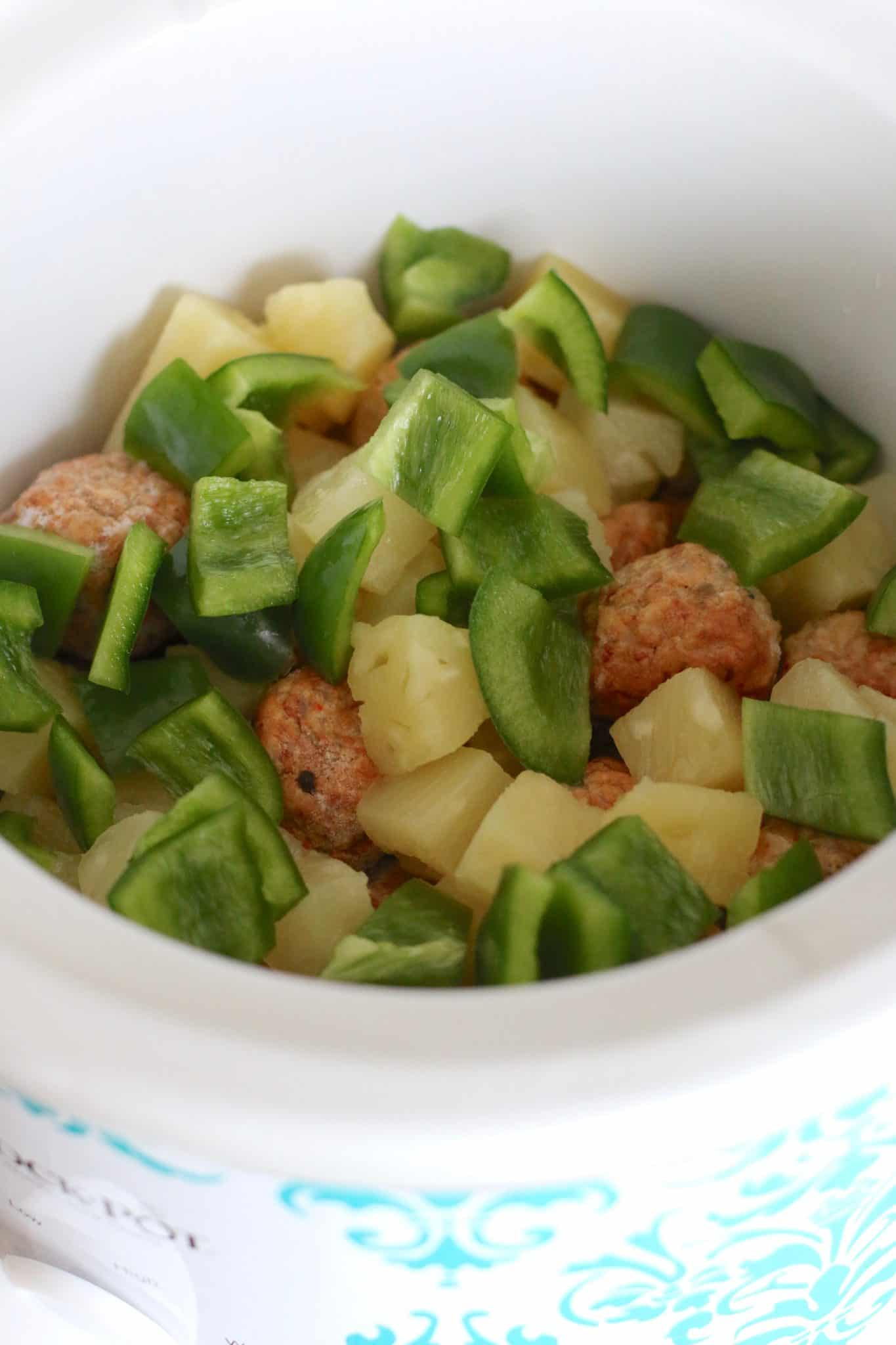frozen meatballs, pineapple chunks, green pepper shown in the bottom of a round slow cooker.