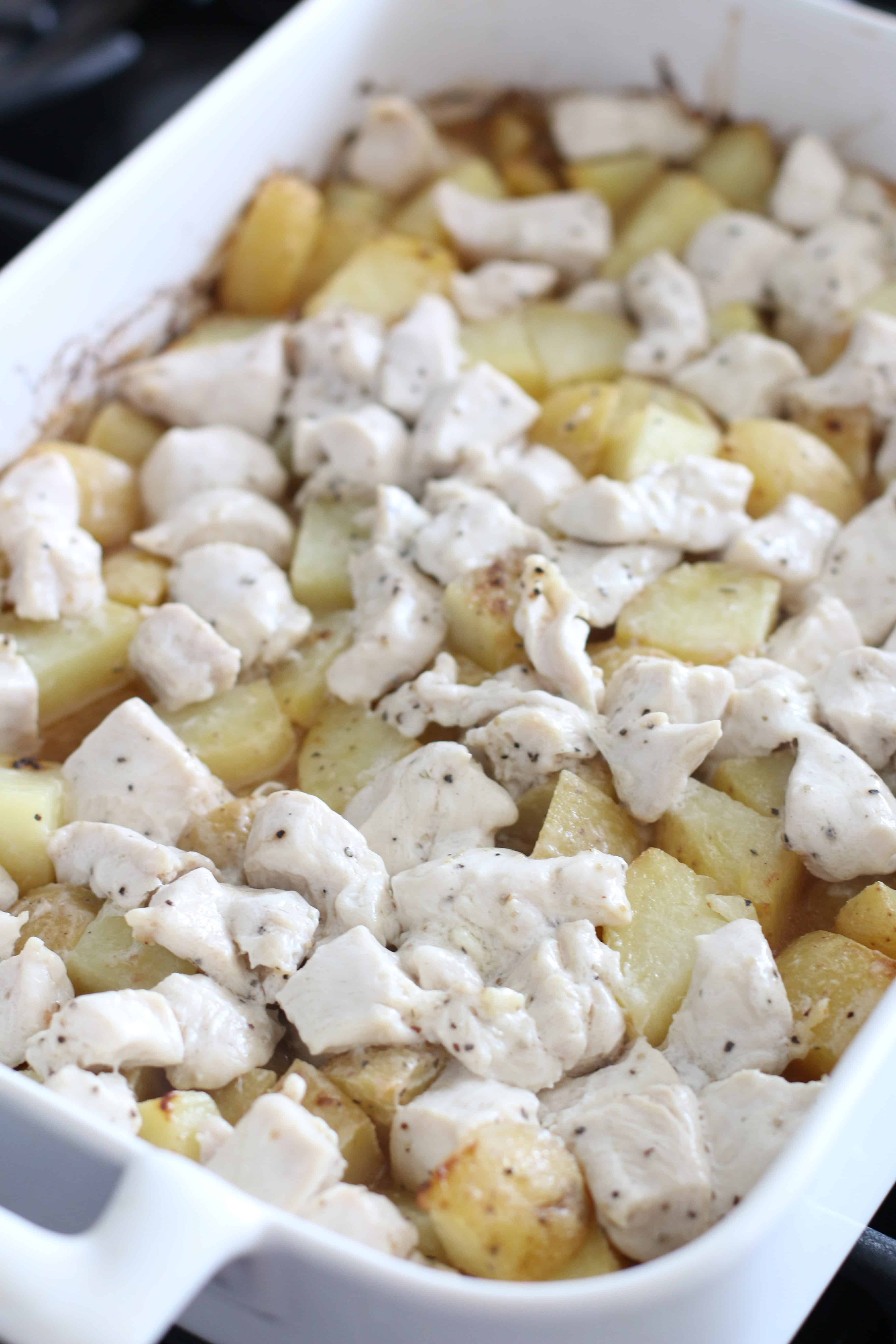 cooked baked chicken and potatoes in a white baking dish.