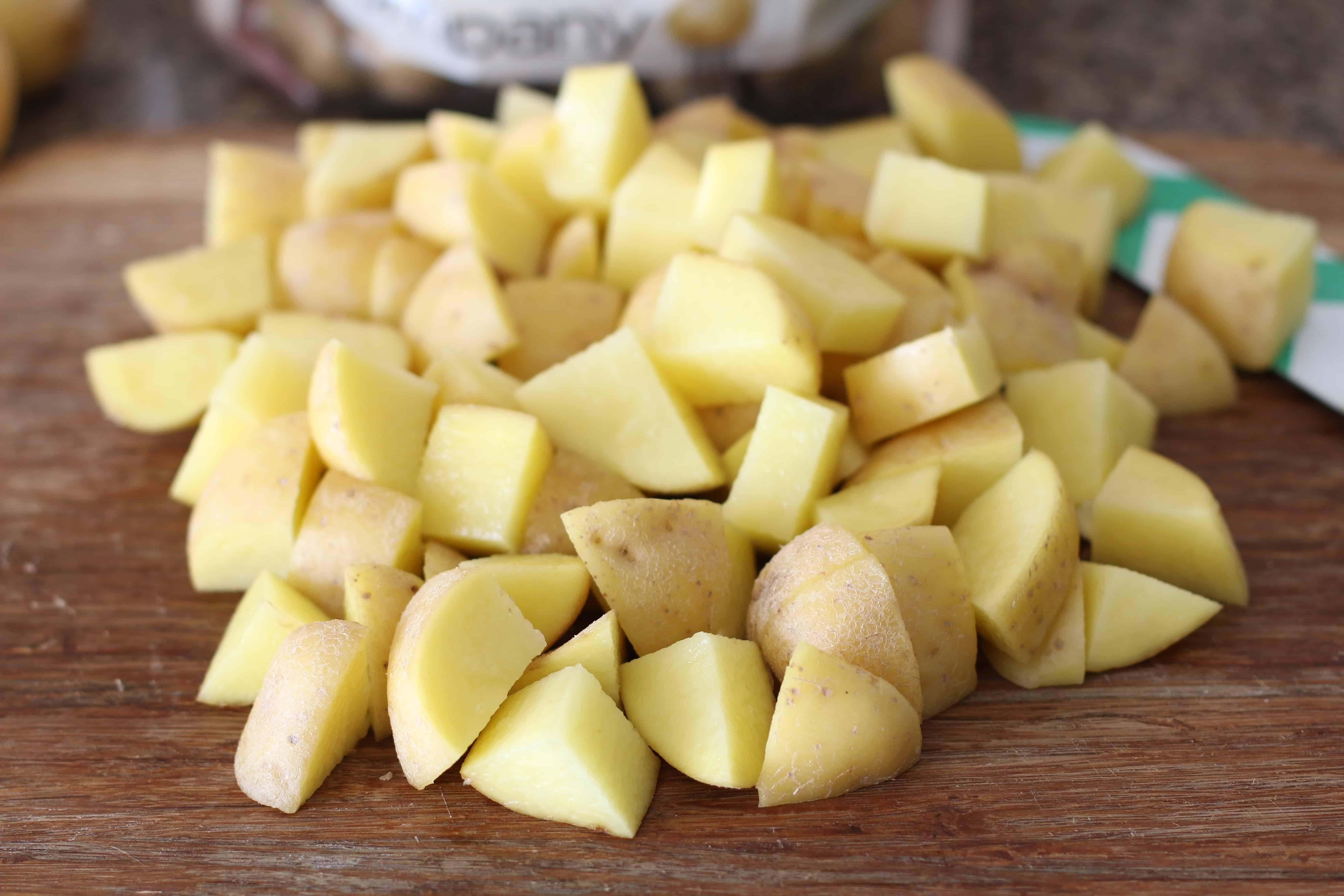 diced potatoes on a wood cutting board.