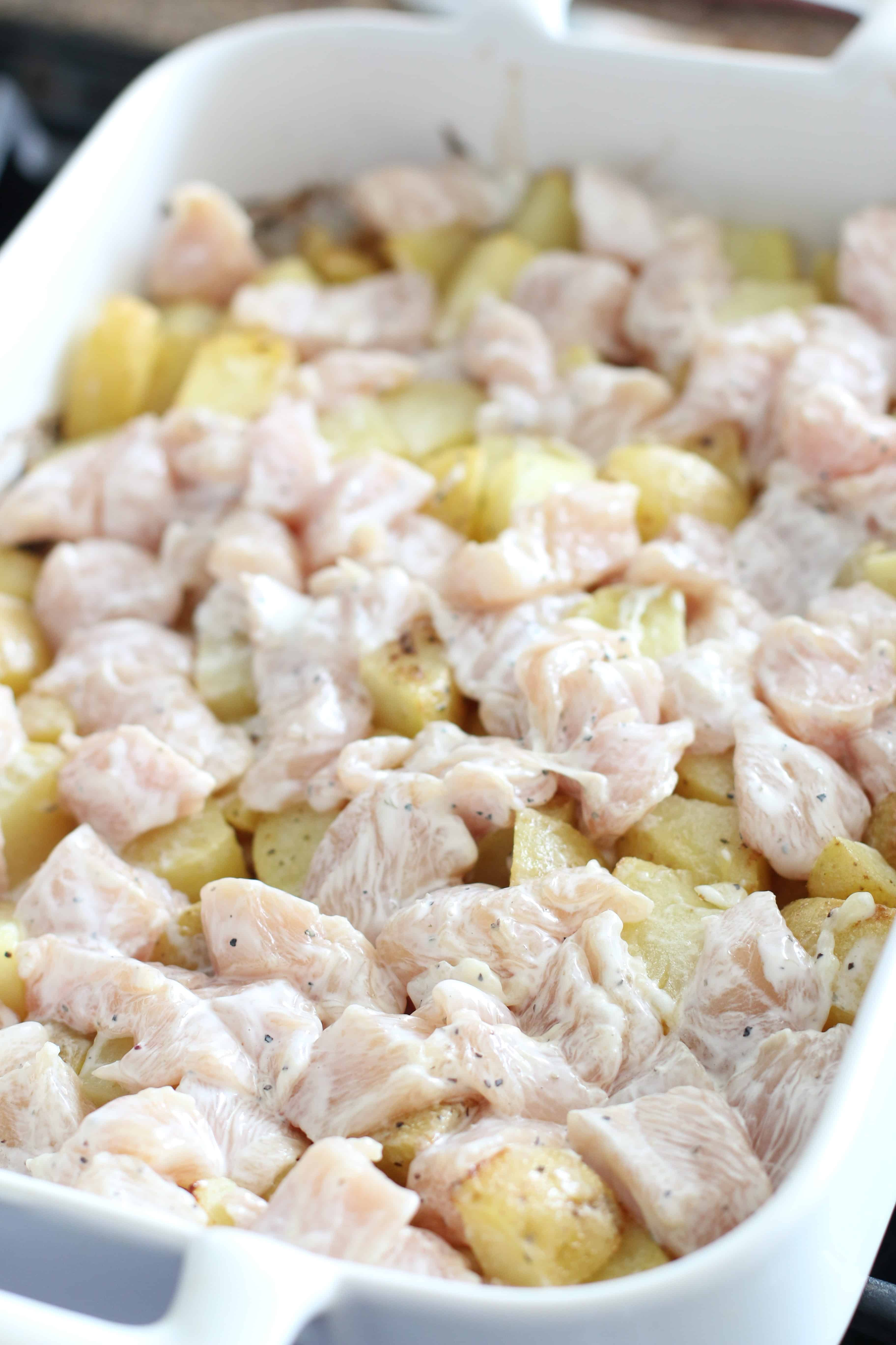 ranch coated chicken and potatoes in a baking dish ready to be cooked.