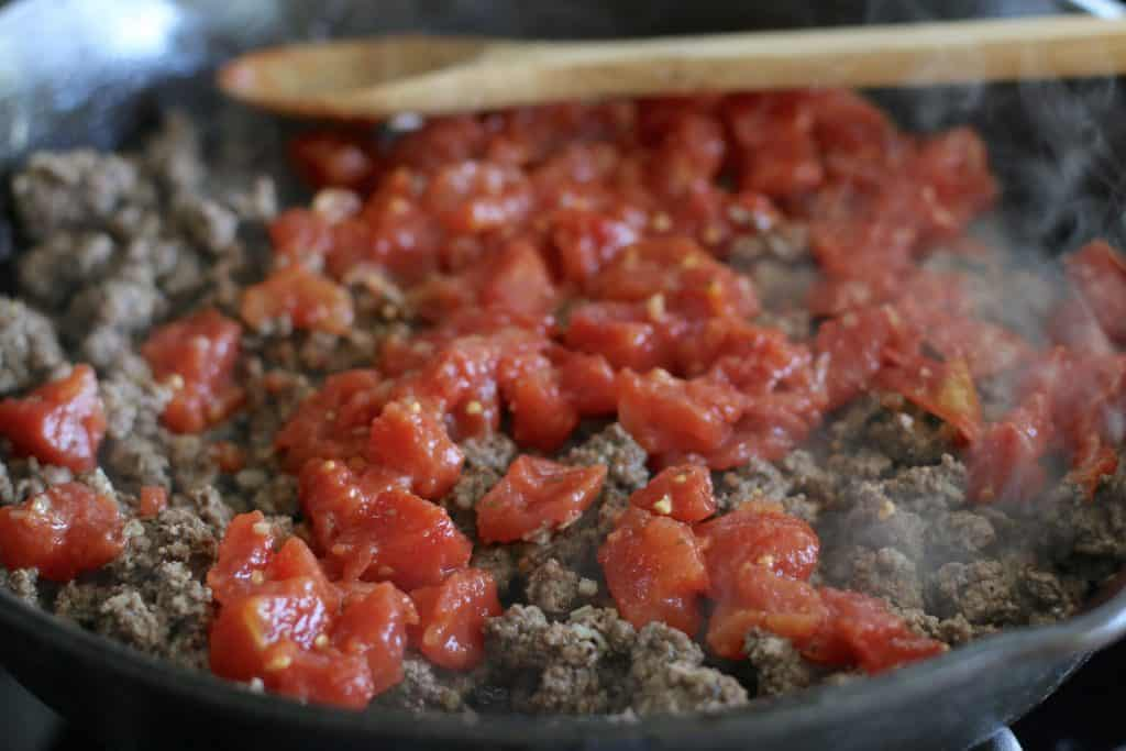 diced tomatoes added to cooked ground beef.