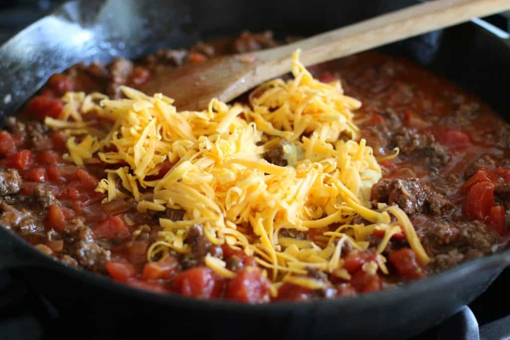 shredded cheddar cheese added to tomatoes and ground beef