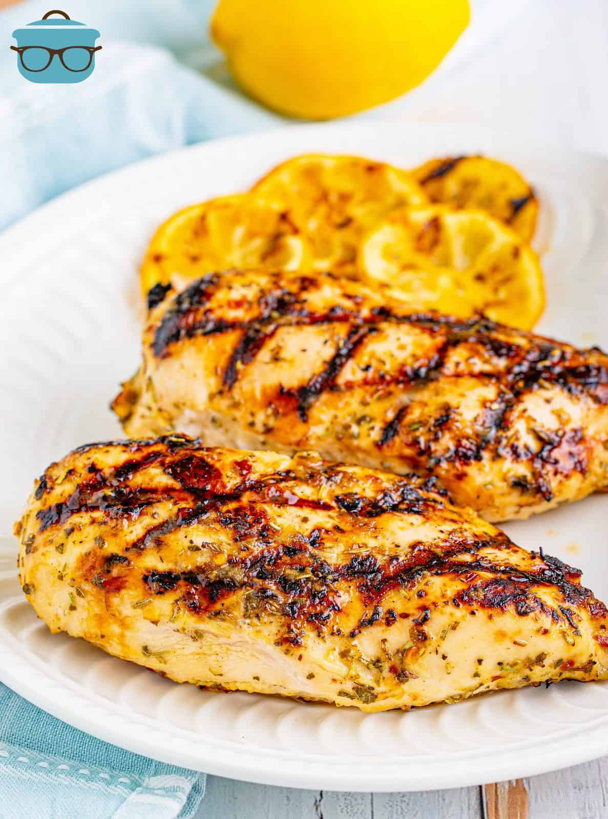 too pieces of grilled lemon garlic chicken show on a white plate.