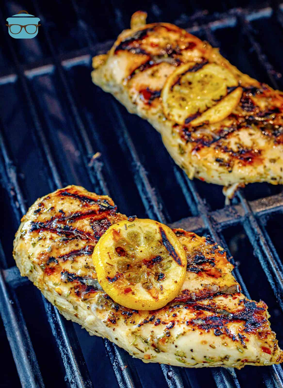 two cooked chicken breasts shown on a grill.