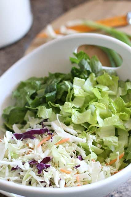 Diced romaine lettuce and shredded packaged cole slaw mix in a white bowl with handles from Target