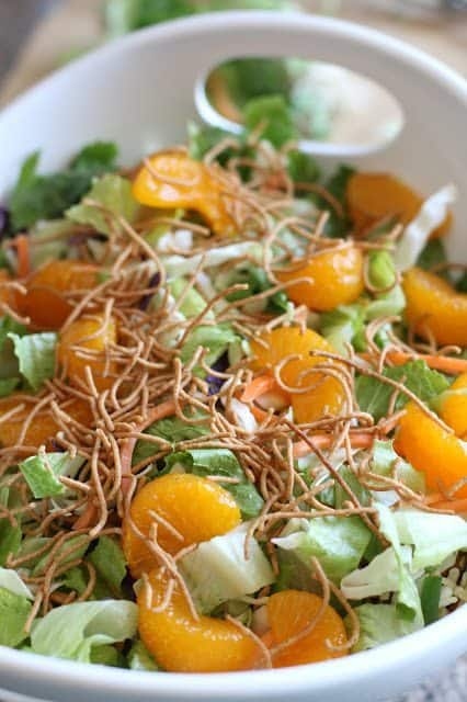 Mandarin oranges, chow mein noodles added to diced romaine lettuce, cole slaw and green onions in a white bowl with handles