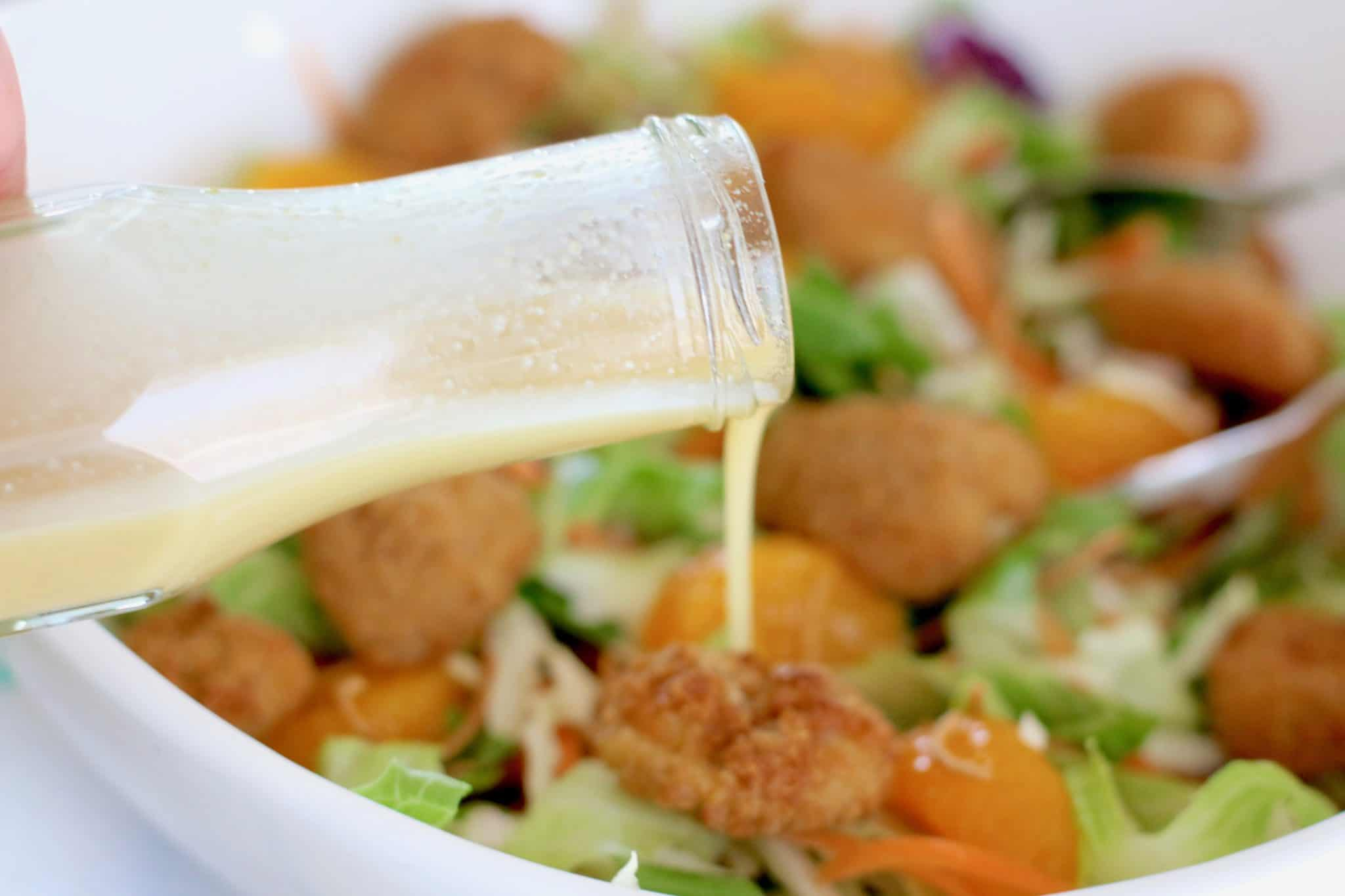 pouring homemade creamy sesame dressing poured on oriental chicken salad.