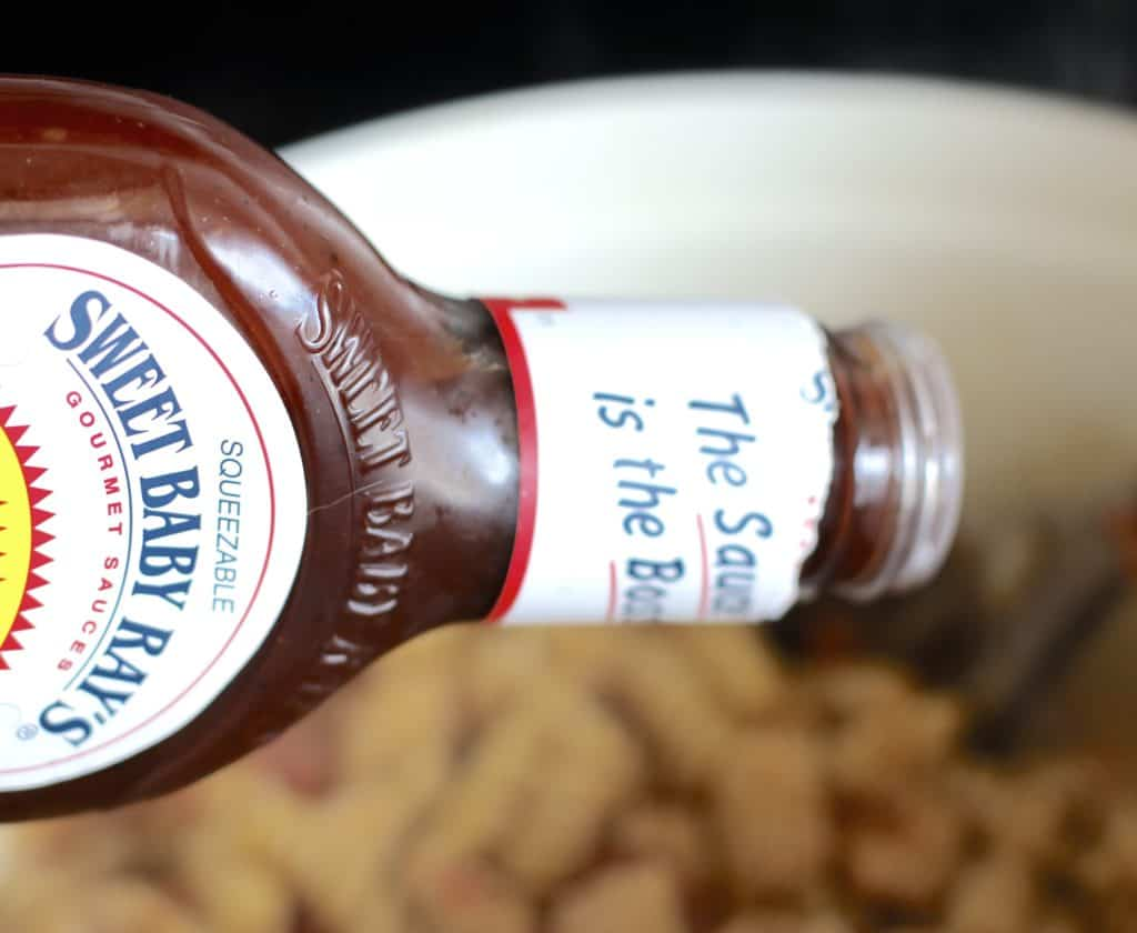 pouring Sweet Baby Ray's BBQ sauce into pasta mixture