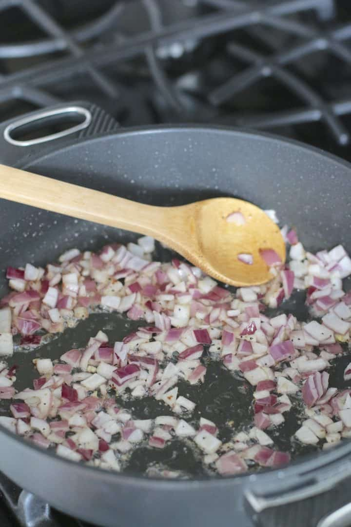diced red onions being cooked in a skillet - shown with a wooden spoon.