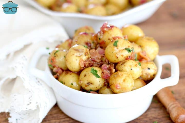 bacon potato salad shown in a small white ramekin with handles and a natural colored napkin to the side.