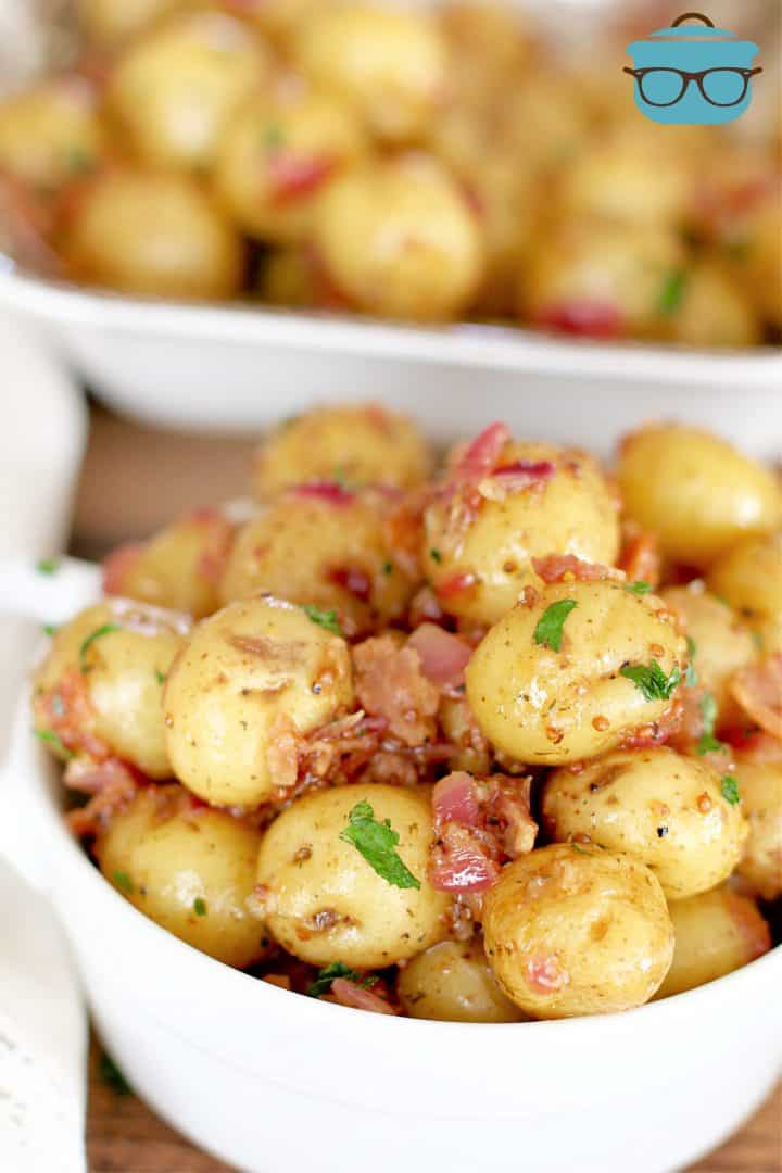 closeup photo of warm bacon potato salad in a small white bowl with a larger serving bowl in the background.