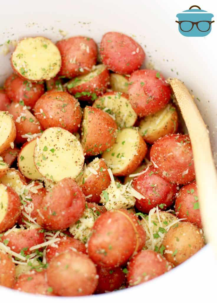 sliced red potatoes with garlic and her seasoning in a white slow cooker and a wooden spoon