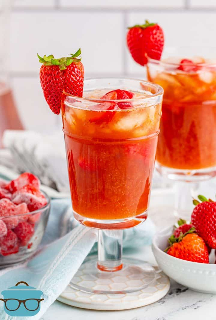 two glasses filled with strawberry tea with fresh strawberry garnishes
