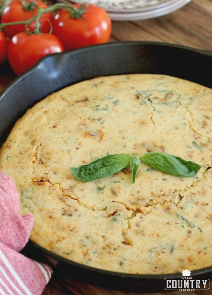 fully baked skillet cornbread in a cast iron skillet and topped with a sprig of basil