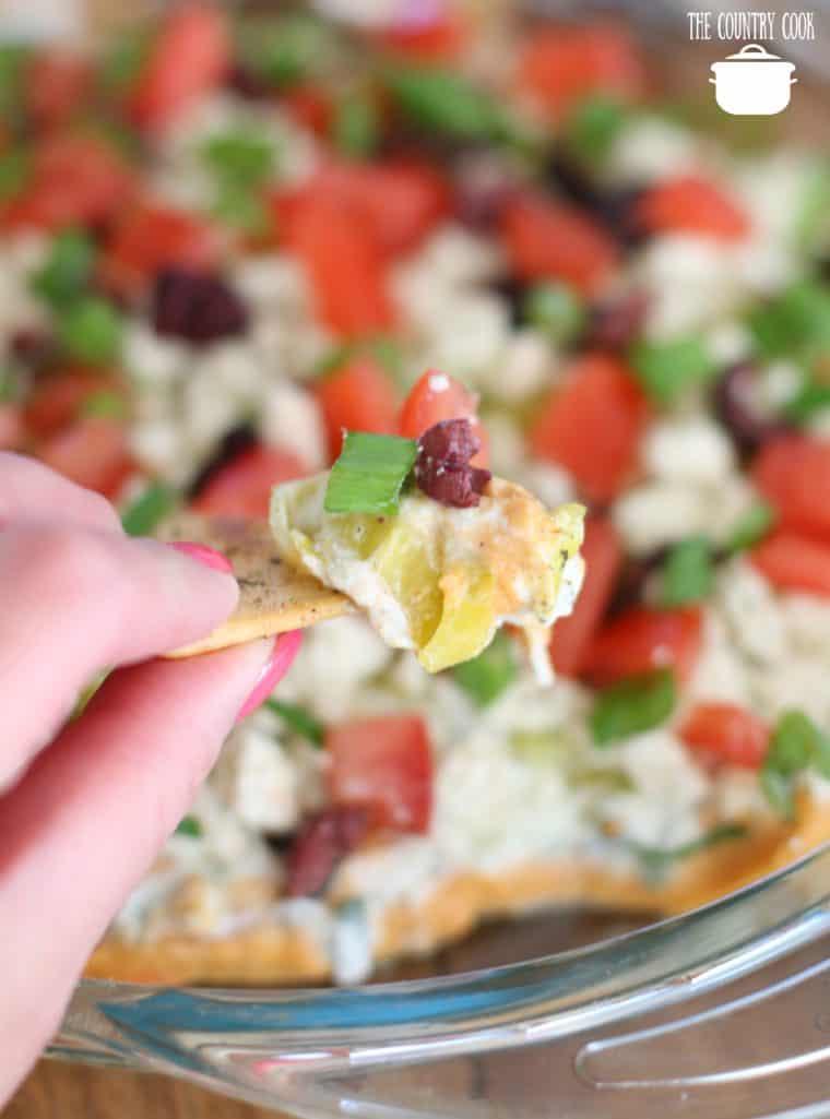 pita chips scooping up Greek layer dip