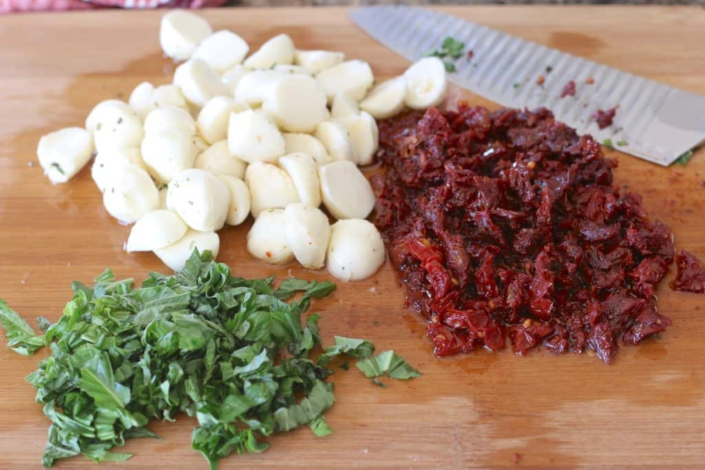 finely chopped basil, chopped sun dried tomatoes and mozzarella balls sliced in half on a cutting board