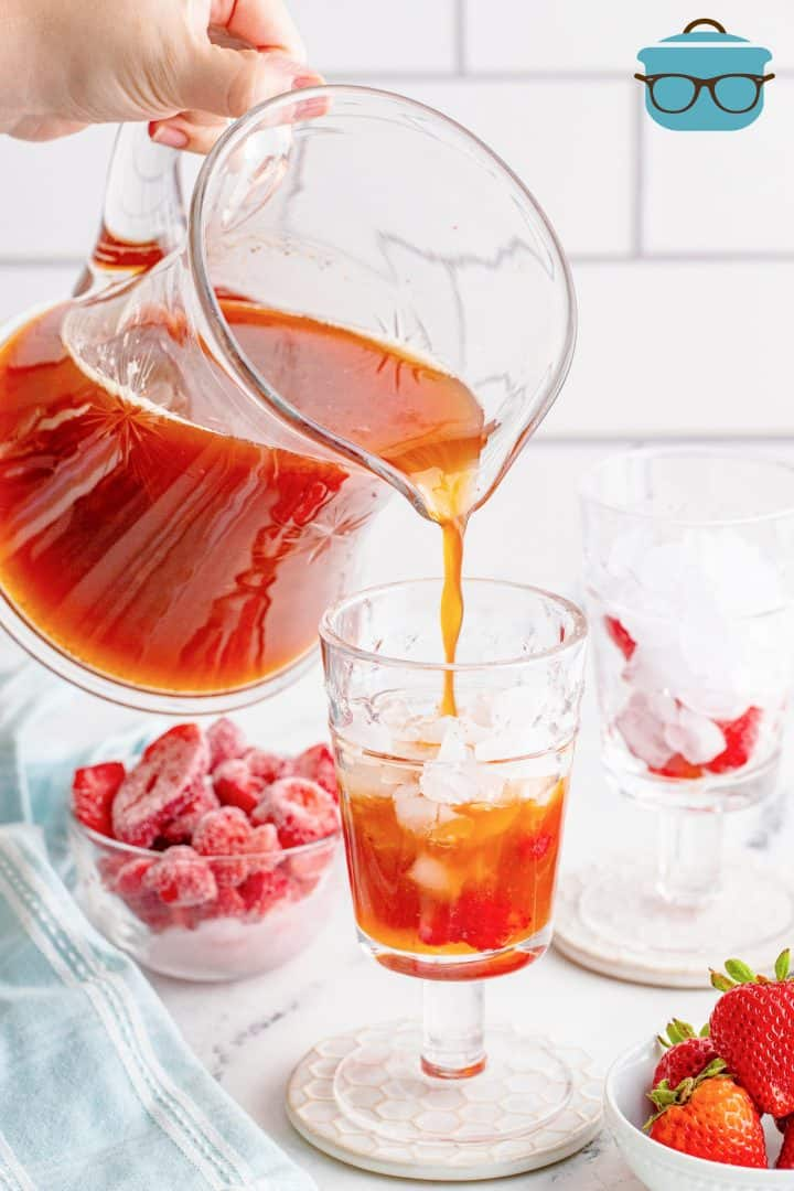 pouring strawberry sweetened iced tea in a glass