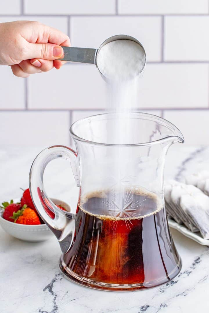 pouring sugar into tea in a large crystal pitcher