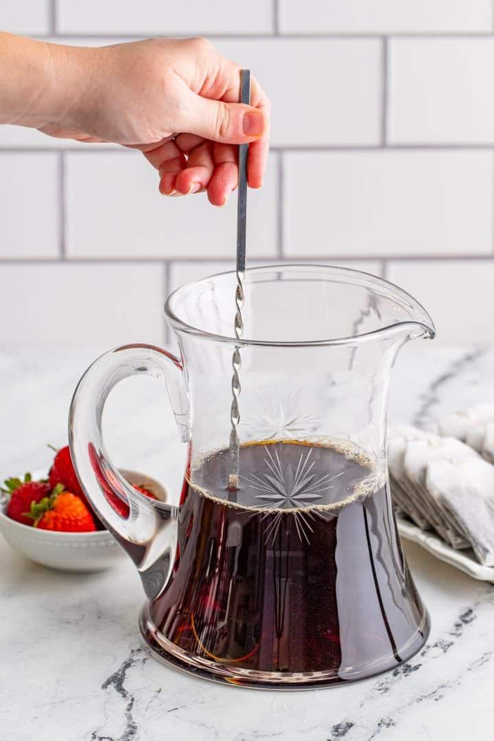 stirring tea with a stirrer to dissolve sugar