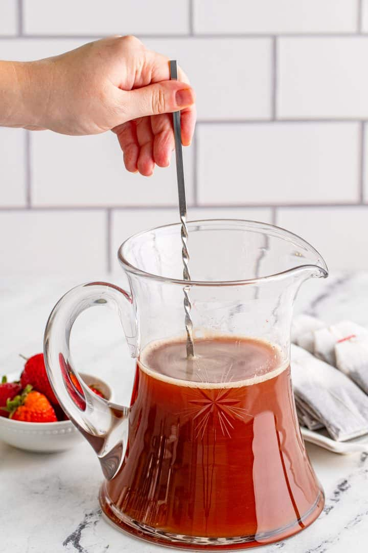 stirring in strawberry pure to brewed tea in a large glass pitcher
