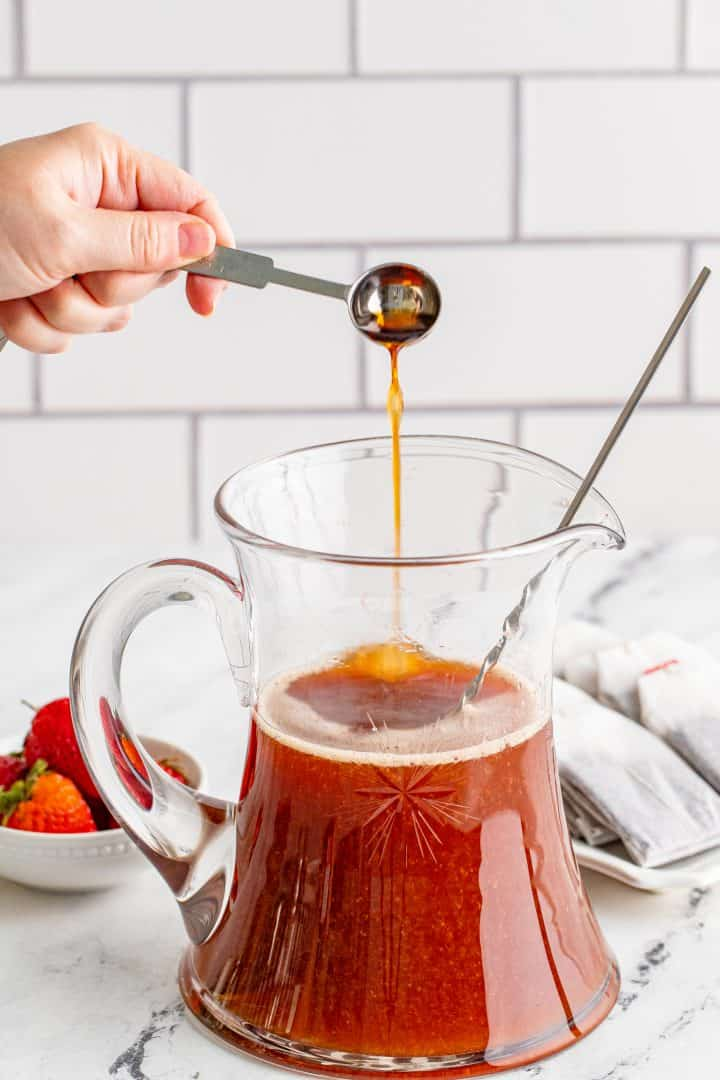 pouring strawberry extract into strawberry tea