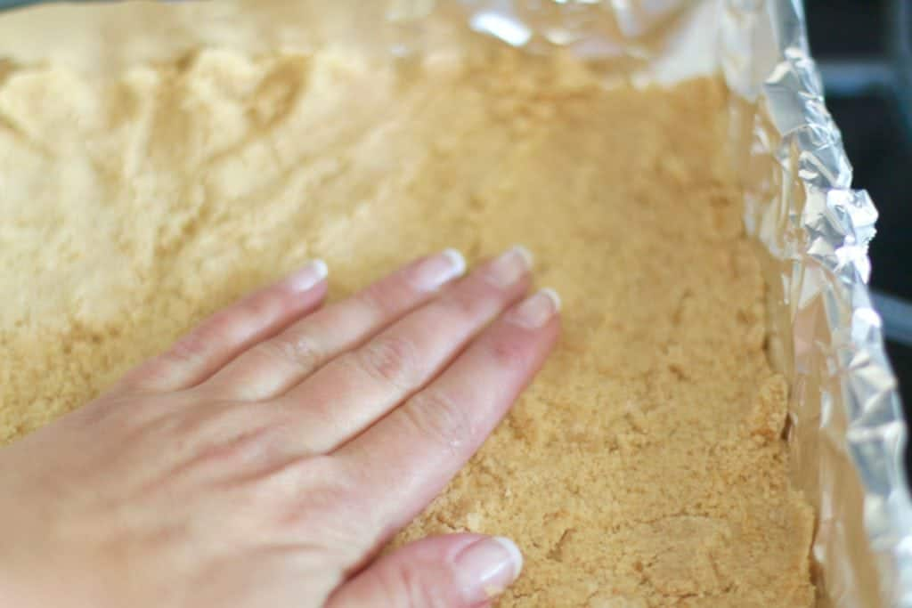 pressing crumbs into aluminum foil lined square baking pan