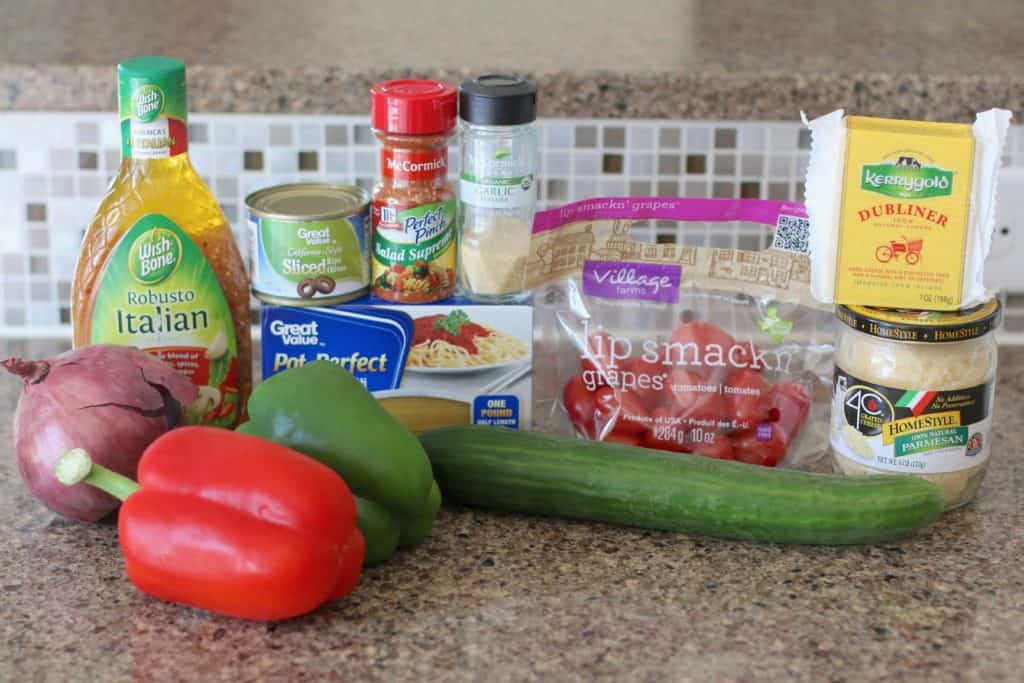 1 (1 lb.) box spaghetti noodles 1 green pepper, diced 1 red pepper, diced 1/2 red onion, sliced thinly 1 English cucumber, sliced 1 cup grape tomatoes, sliced in half 1 (2.25 oz.) can sliced olives, drained 1/2 cup cheddar cheese, cut into small cubes 1/4 cup grated Parmesan cheese 1 tbsp. McCormick Salad Supreme seasoning (optional) 1 tsp. garlic powder 1 (16 oz.) bottle Wish-Bone Italian dressing