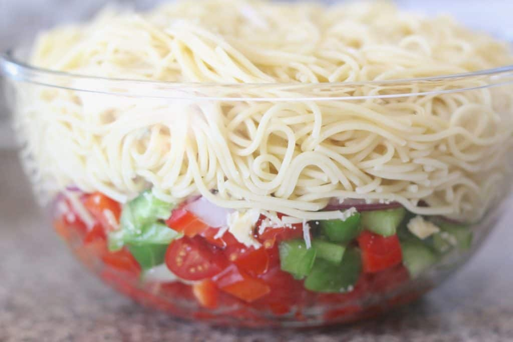 cooked spaghetti noodles, grape tomatoes, peppers, onions in a clear bowl