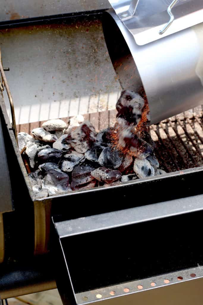 pouring charcoal briquets into the bottom of a charcoal grill