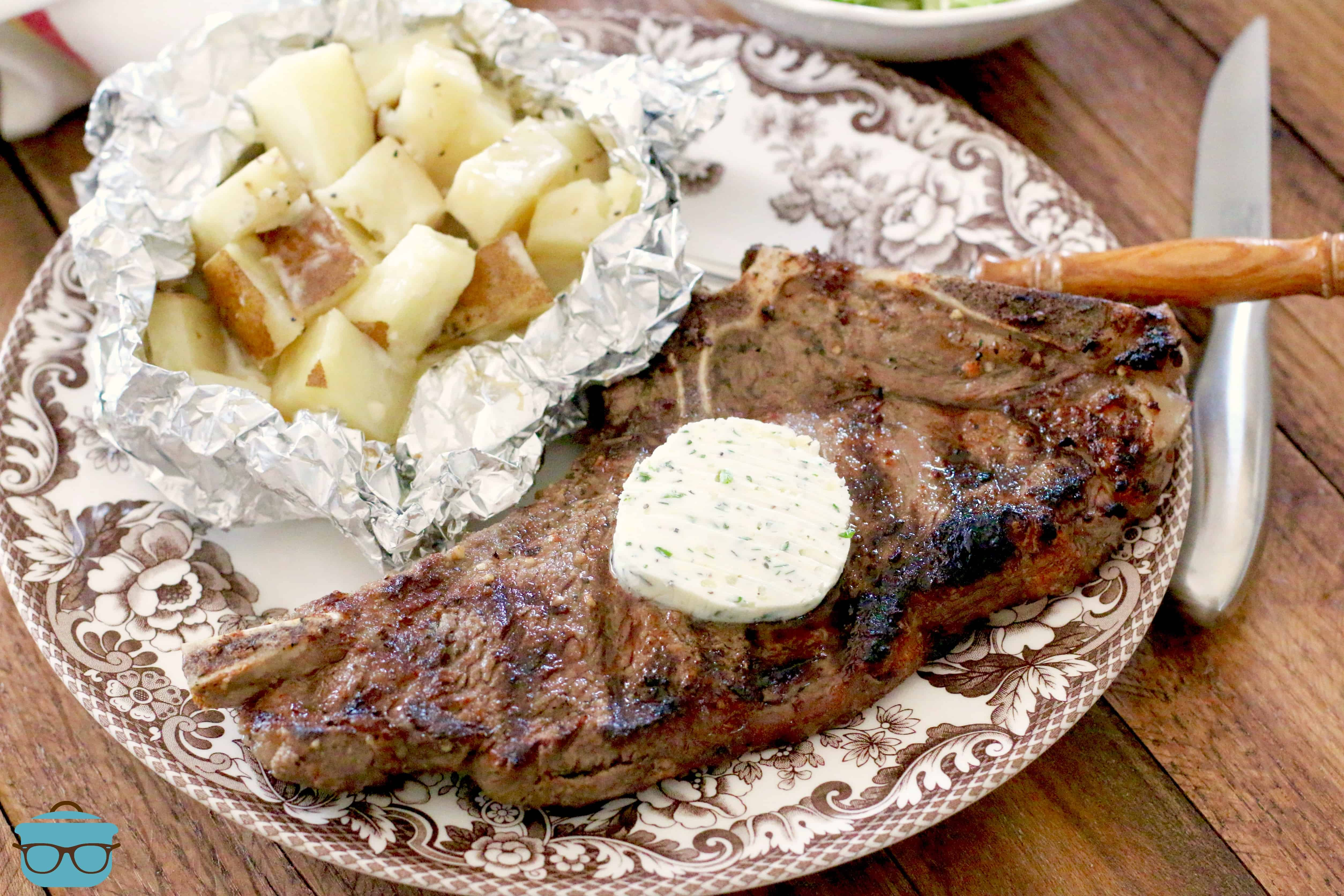 charcoal grilled steaks with garlic herb butter with a side of potatoes on a plate